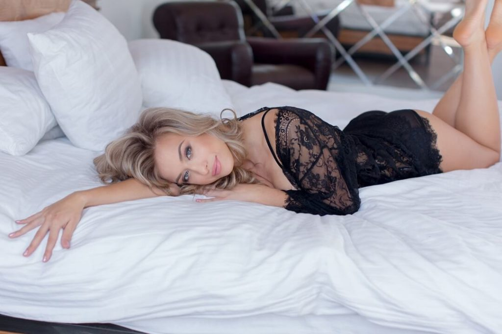 Blonde cougar woman laid on the bed