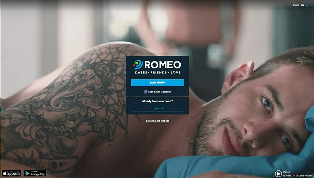 login-screen for planet romeo. handsome young gay single lying in bed after sex looking into the camera. a queer or homosexual  single in background is putting on his pants dressing himself.