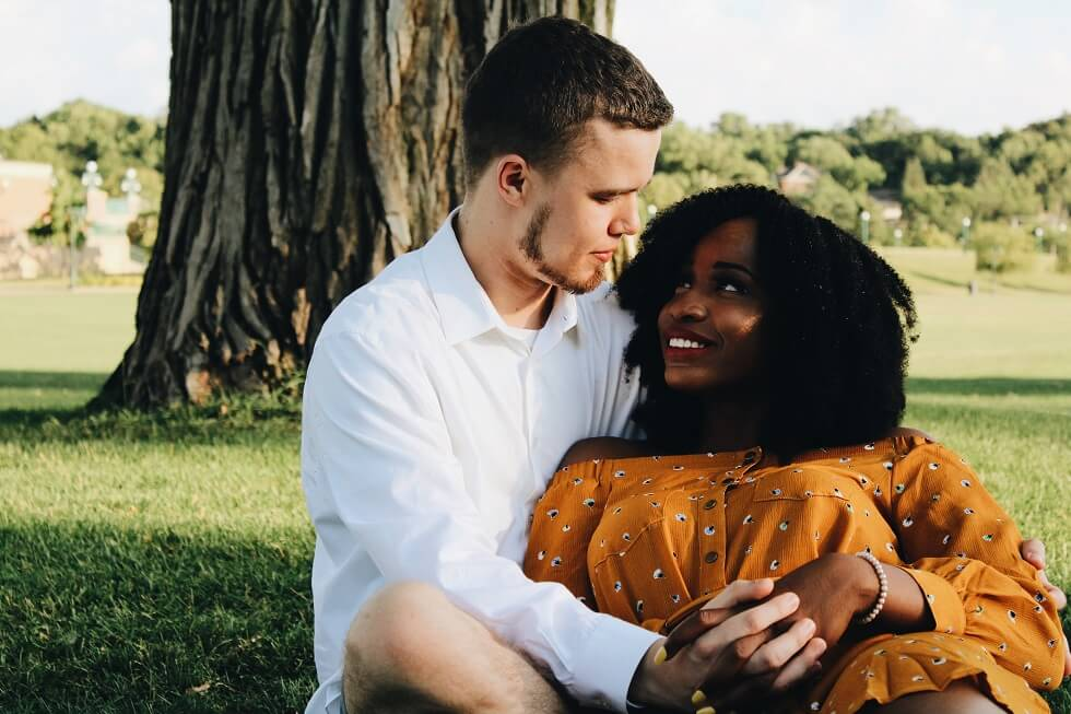 cute interracial couple hanging out in the park