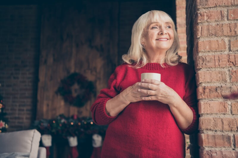 attractive granny smiles and holds a cup