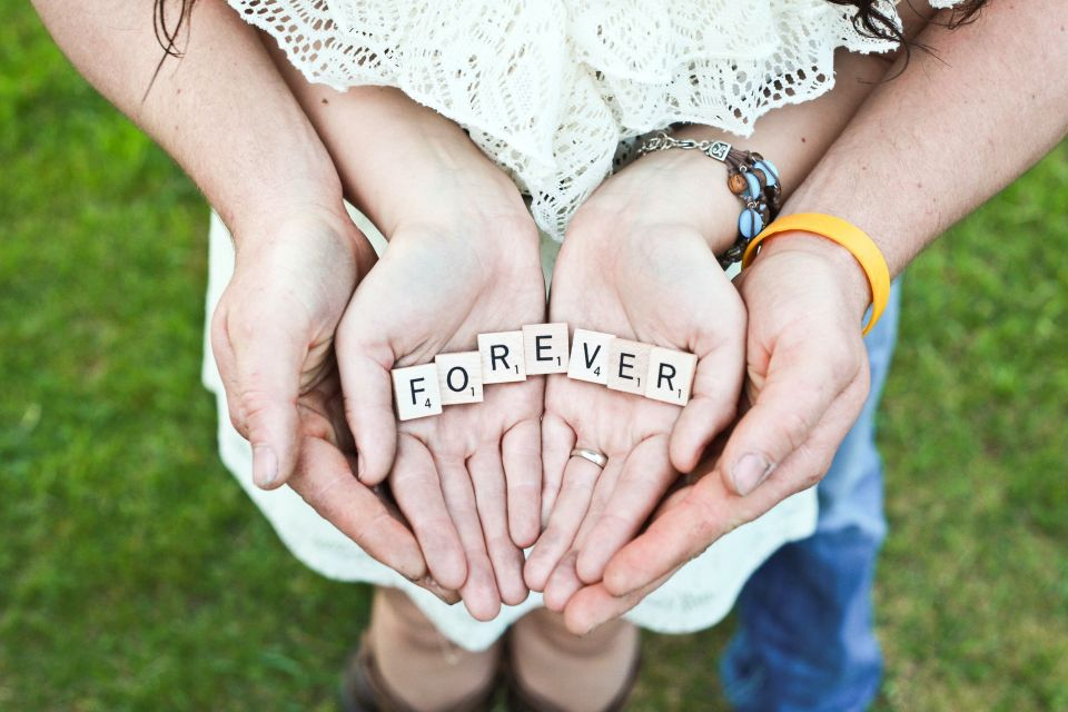 """Couple holding the words """"forever"""" in their hands together."""