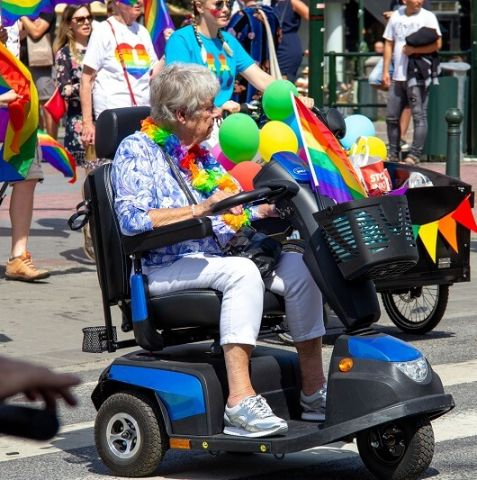 An older woman in a motorized mobility device wearing rainbow flowers in a pride parade.