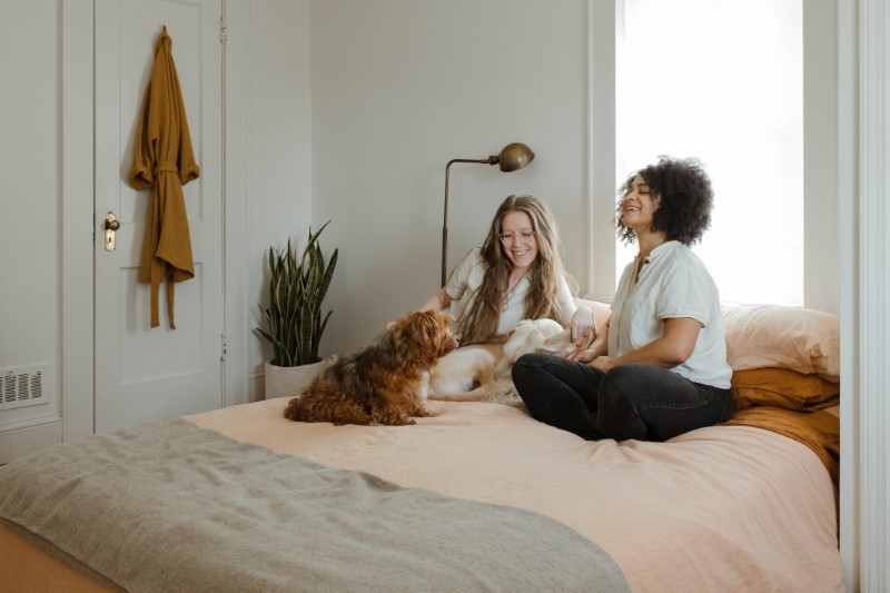 two girlfriends sitting on their bed with their dogs